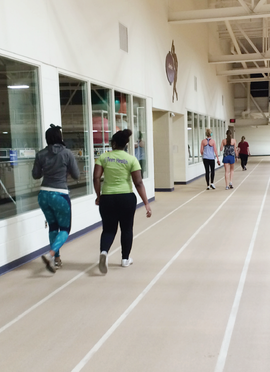 Big Rapids residents Toya Brown (left) and Jasmine Brown (right) circle the track in the Rec Center.